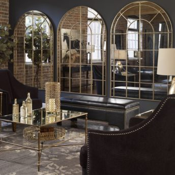 living room with 3 large arch mirrors on wall