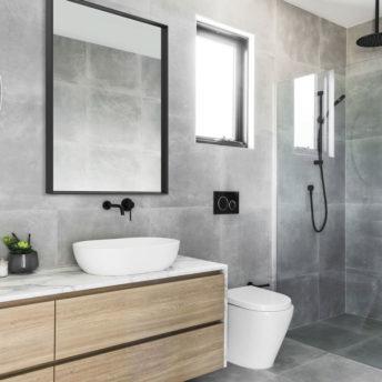 Black Frame REctangular Mirror on Grey Tiled Bathroom Wall