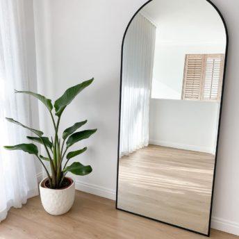 black metal frame arch leaner mirror